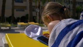 Κορίτσι εφήβων που κάνει ηλιοθεραπεία στο μόνιππο longue και που φαίνεται κοινωνικά δίκτυα σε κινητό απόθεμα βίντεο