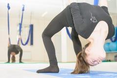 Κορίτσι εφήβων που κάνει το τέντωμα και το σπάγγο, εναέρια γιόγκα Στοκ φωτογραφία με δικαίωμα ελεύθερης χρήσης
