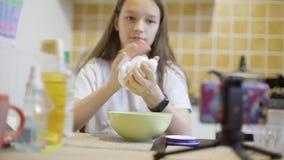 Κορίτσι εφήβων που κάνει χνουδωτό slime στο σπίτι στην κουζίνα απόθεμα βίντεο