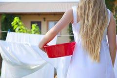 Κορίτσι εφήβων που κρατά μια λεκάνη στα χέρια Στάση στα φύλλα υποβάθρου στη σκοινί για άπλωμα στοκ φωτογραφία με δικαίωμα ελεύθερης χρήσης