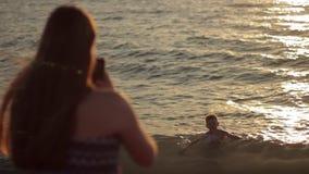 Κορίτσι εφήβων που παίρνει το μικρό παιδί φωτογραφιών με την κινητή έξυπνη τηλεφωνική κάμερα εν πλω ηλιοβασίλεμα απόθεμα βίντεο