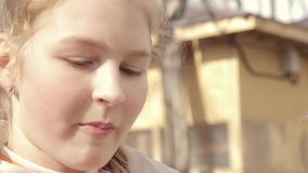 Κορίτσι εφήβων που τρώει doughnut σε ένα υπαίθριο πάρκο απόθεμα βίντεο