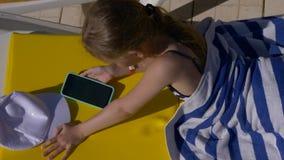 Κορίτσι εφήβων που χρησιμοποιεί το έξυπνο τηλέφωνο κάνοντας ηλιοθεραπεία στο μόνιππο longue στο θέρετρο απόθεμα βίντεο