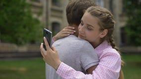 Κορίτσι εφήβων που χρησιμοποιεί το τηλέφωνο, που αγκαλιάζει το φίλο αντί της πραγματικής επικοινωνίας, έννοια φιλμ μικρού μήκους
