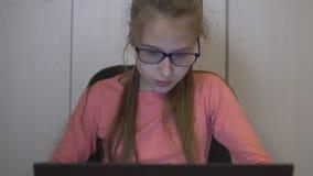 Κορίτσι εφήβων που χρησιμοποιεί το lap-top, στο εσωτερικό, με τις συγκινήσεις απόθεμα βίντεο