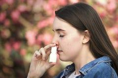 Κορίτσι εφήβων που χρησιμοποιεί inhaler μύτης στο πάρκο πέρα από το ρόδινο λουλούδι στοκ φωτογραφίες με δικαίωμα ελεύθερης χρήσης