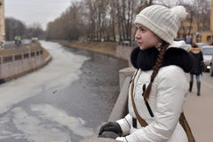 Κορίτσι εφήβων σε ένα άσπρα παλτό και ένα καπέλο στοκ φωτογραφίες