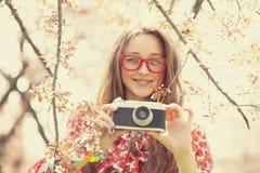 Κορίτσι εφήβων στα γυαλιά με την εκλεκτής ποιότητας κάμερα κοντά στο δέντρο ανθών στοκ εικόνα με δικαίωμα ελεύθερης χρήσης