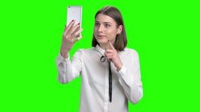 Κορίτσι εφήβων στην άσπρη μπλούζα που μιλά μέσω του εκκέντρου Ιστού του smartphone της φιλμ μικρού μήκους