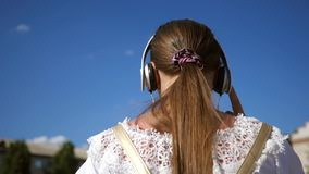 Κορίτσι εφήβων στο άσπρο φόρεμα με τα μακρυμάλλη ταξίδια γύρω από την πόλη ενάντια στο μπλε ουρανό κίνηση αργή οικογενειακό κορίτ απόθεμα βίντεο