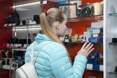 Κορίτσι εφήβων στο κατάστημα phototechnique που εξετάζει την προθήκη στοκ φωτογραφίες με δικαίωμα ελεύθερης χρήσης