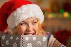 Κορίτσι εφήβων στο κρύψιμο καπέλων santa πίσω από το σημειωματάριο Στοκ Εικόνες