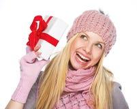 Κορίτσι εφήβων στο χειμερινό καπέλο και μαντίλι που τινάζει παρουσιάζοντας το κιβώτιο Στοκ εικόνες με δικαίωμα ελεύθερης χρήσης
