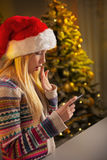Κορίτσι εφήβων σχεδιαγράμματος στο καπέλο santa που γράφει sms Στοκ φωτογραφία με δικαίωμα ελεύθερης χρήσης