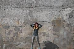 Κορίτσι ικανότητας στα αθλητικά ενδύματα στο υπόβαθρο τοίχων Στοκ Εικόνα