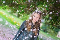 Κορίτσι κάτω από τα μειωμένα πέταλα λουλουδιών Στοκ φωτογραφίες με δικαίωμα ελεύθερης χρήσης