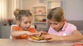 Κορίτσι και αγόρι που κρατούν το κίτρινο μέτωπο donuts των ματιών, που έχουν τη διασκέδαση, ανθυγειινό πρόχειρο φαγητό απόθεμα βίντεο
