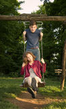 Κορίτσι και αγόρι σε μια ταλάντευση που έχει τη διασκέδαση Στοκ Εικόνες