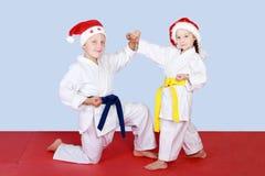 Κορίτσι και αγόρι στα καπέλα Άγιος Βασίλης που κάνουν το χτύπημα και τους φραγμούς Στοκ φωτογραφία με δικαίωμα ελεύθερης χρήσης
