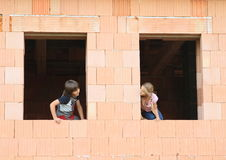 Κορίτσι και αγόρι στα παράθυρα Στοκ φωτογραφία με δικαίωμα ελεύθερης χρήσης