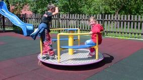 Κορίτσι και αγόρι στην παιδική χαρά Τα παιδιά παίζουν στη διασταύρωση κυκλικής κυκλοφορίας φιλμ μικρού μήκους