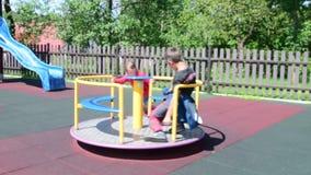 Κορίτσι και αγόρι στην παιδική χαρά Τα παιδιά παίζουν στη διασταύρωση κυκλικής κυκλοφορίας απόθεμα βίντεο