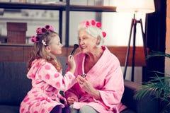 Κορίτσι και γιαγιά που φορούν τους κυλίνδρους τρίχας που κάνουν makeup από κοινού στοκ φωτογραφία με δικαίωμα ελεύθερης χρήσης