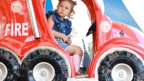 Κορίτσι και γύροι παιδιών ένα αυτοκίνητο πυρκαγιάς στο πάρκο για την ψυχαγωγία Έλξη για τα παιδιά απόθεμα βίντεο