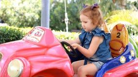 Κορίτσι και γύροι παιδιών ένα ηλεκτρικό αυτοκίνητο στο πάρκο για την ψυχαγωγία Έλξη για τα παιδιά απόθεμα βίντεο
