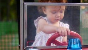 Κορίτσι και γύροι παιδιών ένα ηλεκτρικό αυτοκίνητο στο πάρκο για την ψυχαγωγία Έλξη για τα παιδιά playground απόθεμα βίντεο