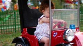 Κορίτσι και γύροι παιδιών ένα ηλεκτρικό αυτοκίνητο στο πάρκο για την ψυχαγωγία Έλξη για τα παιδιά playground φιλμ μικρού μήκους
