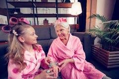 Κορίτσι και η γιαγιά της που φορούν το αίσθημα κυλίνδρων τρίχας ευτυχές από κοινού στοκ εικόνες