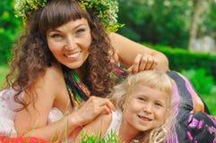 Κορίτσι και η μαμά της ανάμεσα στην πράσινη χλόη στοκ εικόνες