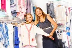 Κορίτσι και η μητέρα της που κρατούν το άσπρο πουλόβερ Στοκ Φωτογραφίες