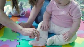 Κορίτσι και μητέρα μικρών παιδιών που παίζουν καθμένος στο πάτωμα απόθεμα βίντεο