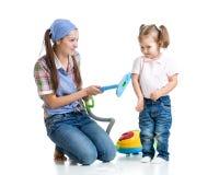 Κορίτσι και μητέρα παιδιών με την ηλεκτρική σκούπα Στοκ Φωτογραφία