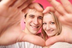 Κορίτσι και ο φίλος της που κατασκευάζουν την καρδιά Στοκ φωτογραφία με δικαίωμα ελεύθερης χρήσης