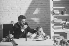 Κορίτσι και πατέρας στο δωμάτιο μελέτης στο άσπρο υπόβαθρο τούβλου Στοκ Φωτογραφία