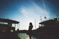 Κορίτσι και σκάφη σκιαγραφιών στη θάλασσα Στοκ Φωτογραφία