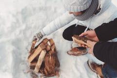 Κορίτσι και τεθειμένο αγόρι καυσόξυλο στο χιόνι Στοκ Εικόνες
