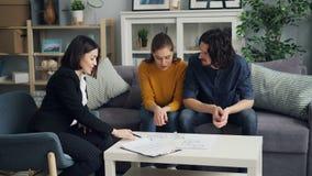 Κορίτσι και τύπος που εξετάζουν τα επίπεδα σχέδια που μιλούν στη συνεδρίαση realtor στον πίνακα στο εσωτερικό απόθεμα βίντεο