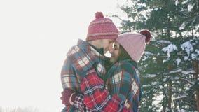 Κορίτσι και τύπος στον εναγκαλισμό ενός ηλιόλουστου χειμερινού δάσους ημέρας, φλόγα φωτός του ήλιου φιλμ μικρού μήκους
