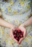 Κορίτσι κεράσια στα όμορφα φορεμάτων derzhet στα χέρια της στοκ φωτογραφία με δικαίωμα ελεύθερης χρήσης