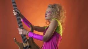 Κορίτσι κομμάτων Disco που χορεύει και που θέτει με την κιθάρα, σε αργή κίνηση φιλμ μικρού μήκους