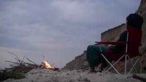 Κορίτσι κοντά στην πυρά προσκόπων στην παραλία απόθεμα βίντεο