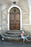 Κορίτσι κοντά στην πόρτα ενός παλαιού κτηρίου Στοκ Φωτογραφία