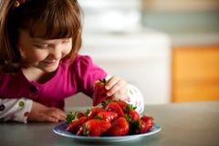 Κορίτσι κουζινών: Πεινασμένος για τις φράουλες στοκ εικόνες