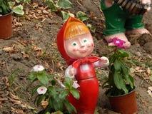 κορίτσι κουκλών που στέκεται μεταξύ flowerpots Στοκ Εικόνες