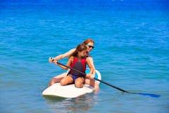 Κορίτσι κυματωγών κουπιών παιδιών surfer με τη σειρά στην παραλία στοκ εικόνες με δικαίωμα ελεύθερης χρήσης
