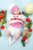 Κορίτσι μαγείρων μωρών που φορά το καπέλο αρχιμαγείρων με τα φρέσκα λαχανικά. Στοκ Φωτογραφία